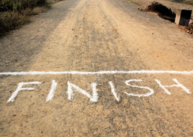 Road with word FINISH written in chalk and a chalk line for a race to express finishing the race as in the year 2020- Bosun